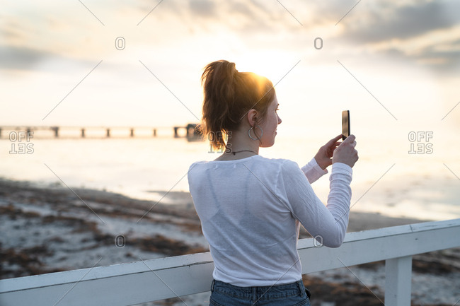Young woman taking photo of ocean sunrise