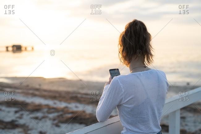 Backside view of girl holding smartphone on pier in front of golden ocean sunrise