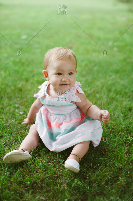 Portrait of a one year old baby girl sitting in grass