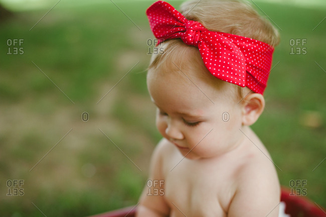 One year old baby girl with a red bow on her head