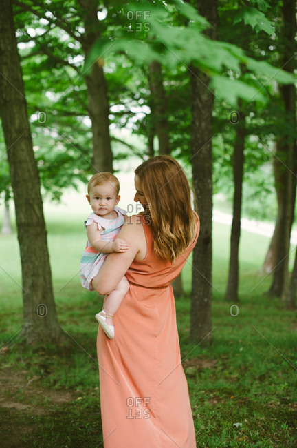 Mother holding her baby girl in front of trees