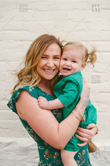 Happy mother holding daughter in front of a white brick wall