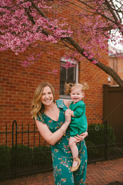 Mother holding daughter under tree with pink blossoms