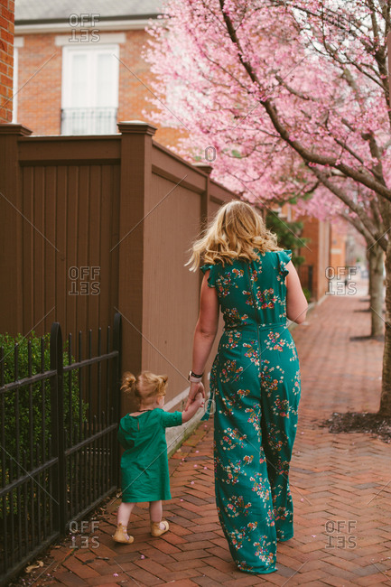 Mother walking with daughter on sidewalk in spring