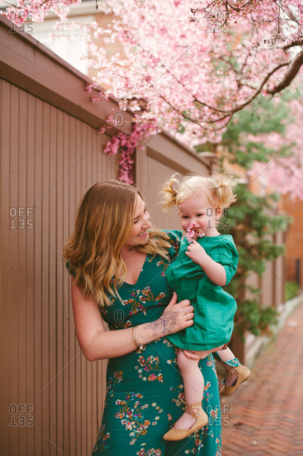 Baby smelling pink blossoms in mother's arms