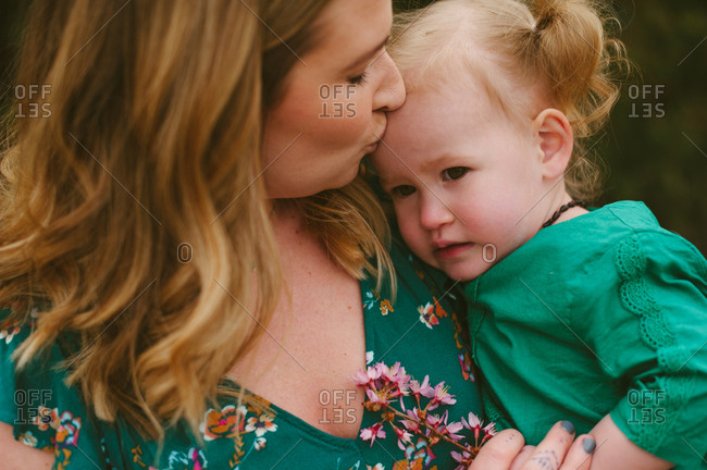 Mother kissing baby's forehead