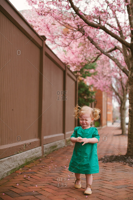 Sad baby girl standing on sidewalk in spring