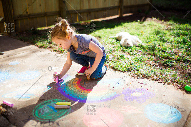 Blonde little girl drawing rainbow with sidewalk chalk