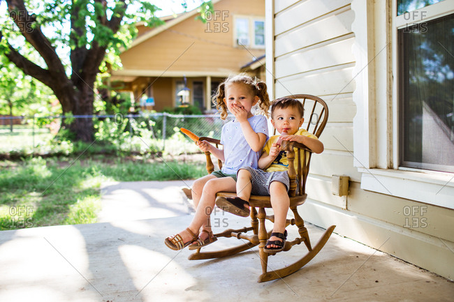 Two kids in a rocking chair eating popsicles
