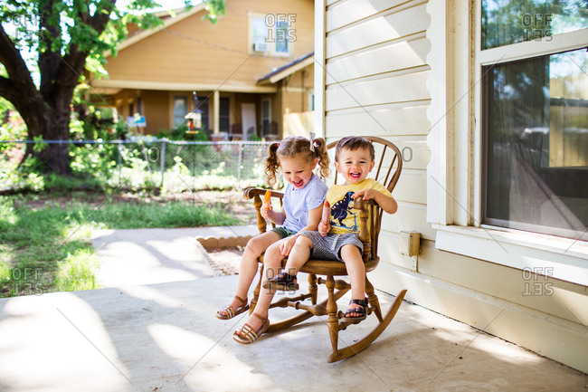 Two happy children in a rocking chair eating popsicles