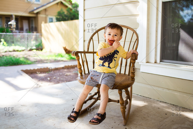 Toddler boy in a rocking chair eating popsicles