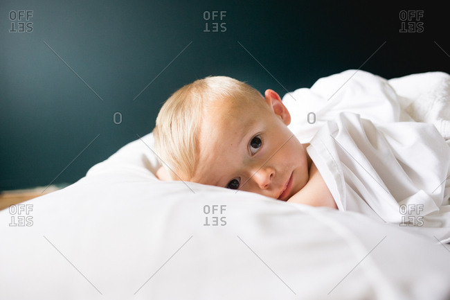 Young boy laying on a bed with white sheets looking at the camera with big brown eyes