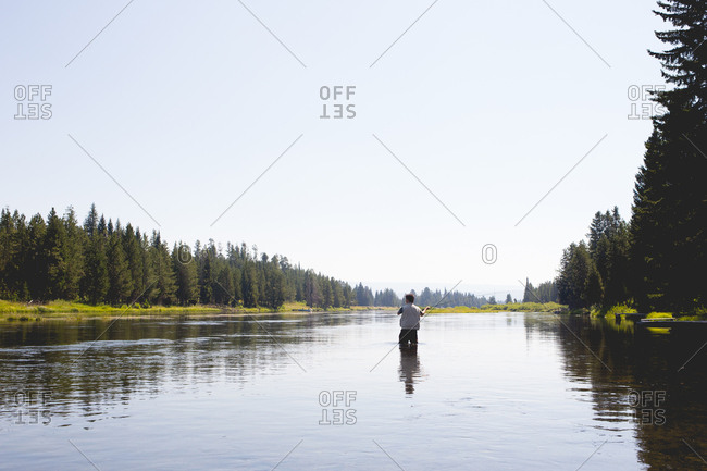 Man standing in the middle of a large river back casting a fly fishing rod.