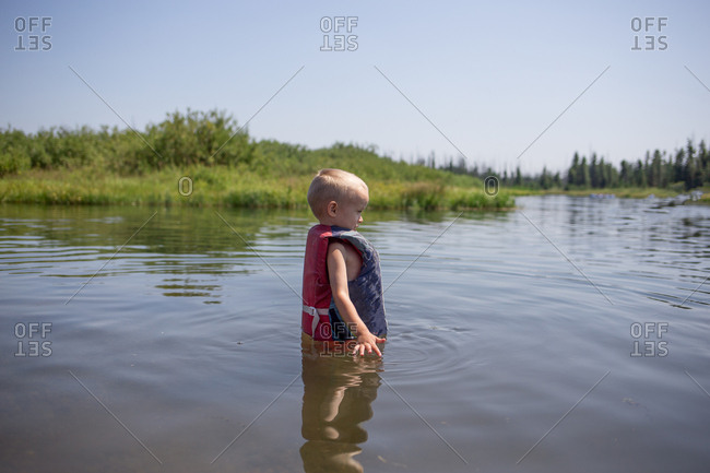 Young boy standing in a river wearing a life jacket