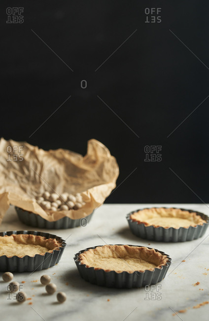 Blind baked pastry cups on marble counter
