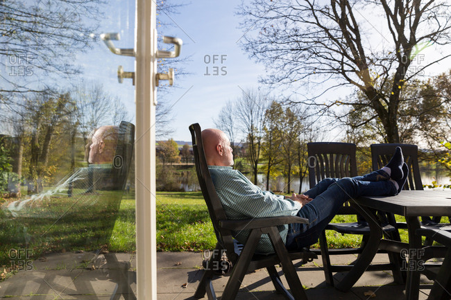 Senior man relaxing in on vacation home terrace with feet on table