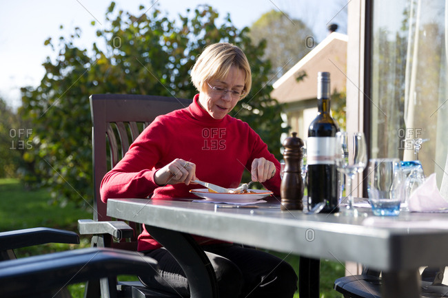 Senior woman dining  at outdoor table