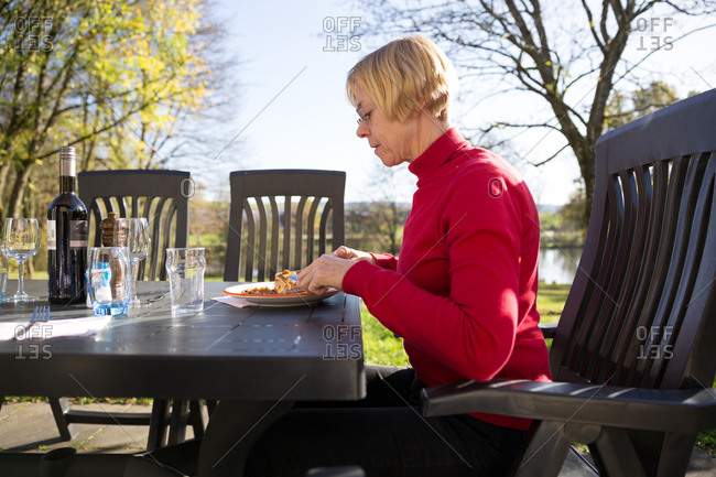 Side view of mature woman having meal outside