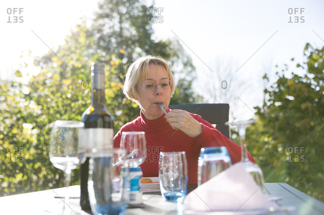 Older woman eating meal at table in nature