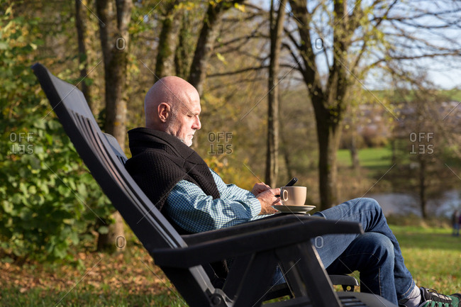 Senior man relaxing in chair outside with mobile phone and cup of coffee