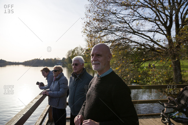 Family of three generations standing on pier near lake