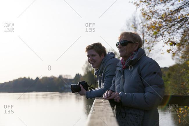 Grandmother and granddaughter looking at lake