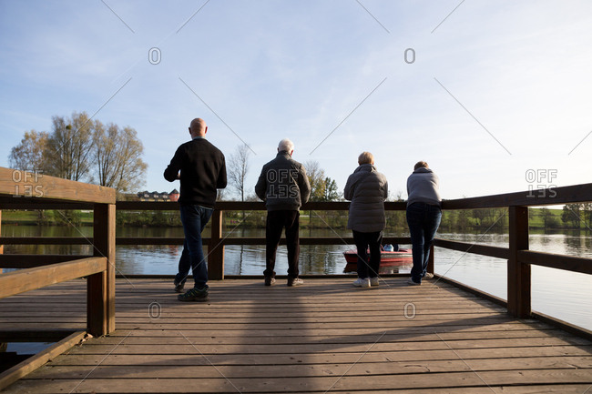 Family of parents and grandparents looking at kids on the lake