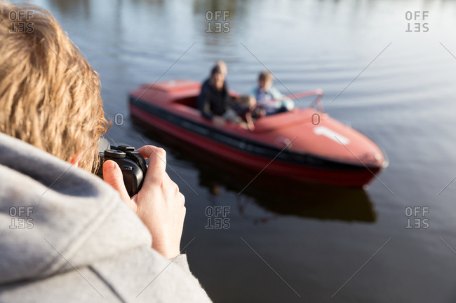 Mother taking pictures of kids in boat