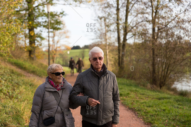 Older senior couple walking in nature and holding arms