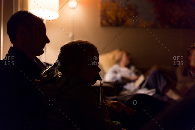 Silhouette of grandfather and grandchild in cozy living room