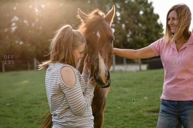 Girl petting horse under supervision of adult woman