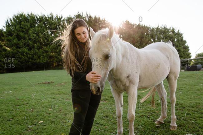 Girl petting horse.