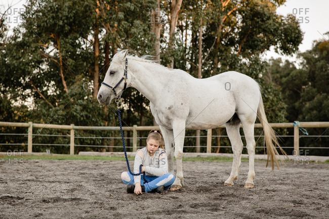 Girl sitting with horse in arena