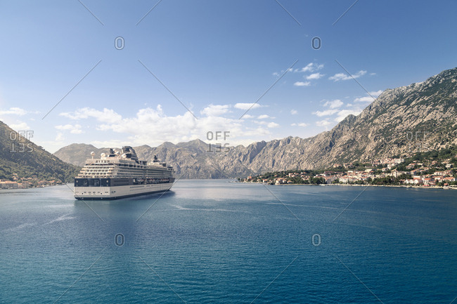 Bay of Kotor, Montenegro - June 25, 2015: Cruise ship sailing in sea against mountains and sky