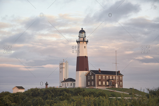 Montauk, New York, USA - August 18, 2012: Montauk Point Light on field against cloudy sky during sunset