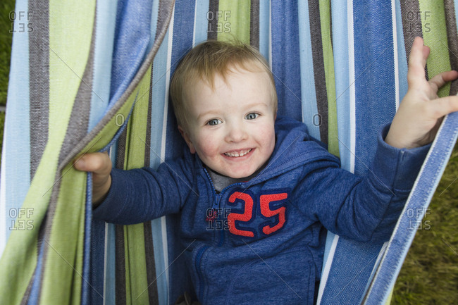 Overhead portrait of cheerful boy lying in hammock at backyard