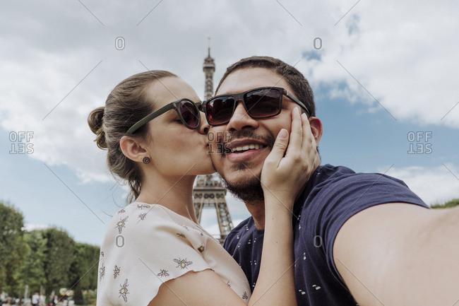 Portrait of girlfriend kissing boyfriend against Eiffel Tower in city