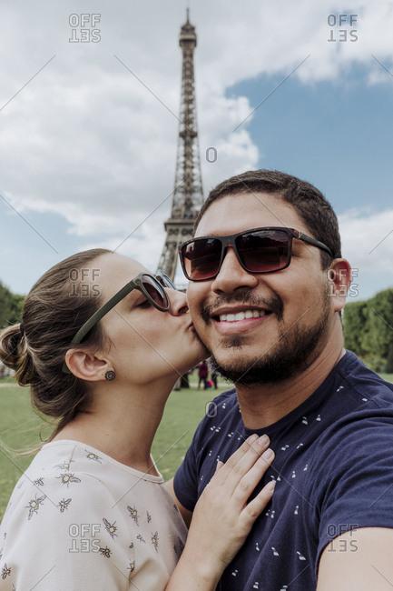 Portrait of loving girlfriend kissing smiling boyfriend against Eiffel Tower in city