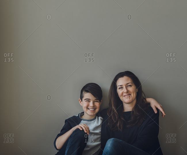 Portrait of happy mother with son sitting by wall at home