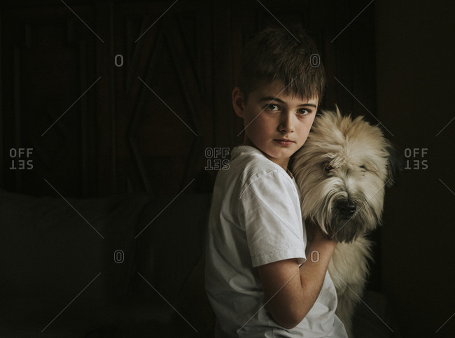 Portrait of boy with dog standing in darkroom at home