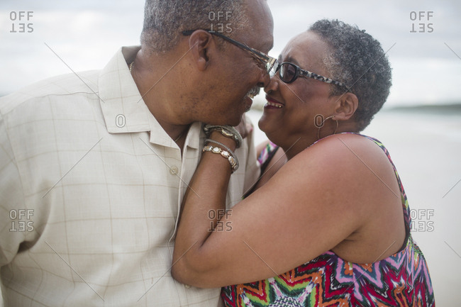 Happy senior couple romancing at beach against cloudy sky