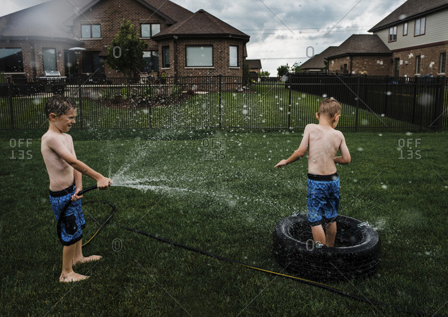 Shirtless boy spraying water on brother with garden hose at park