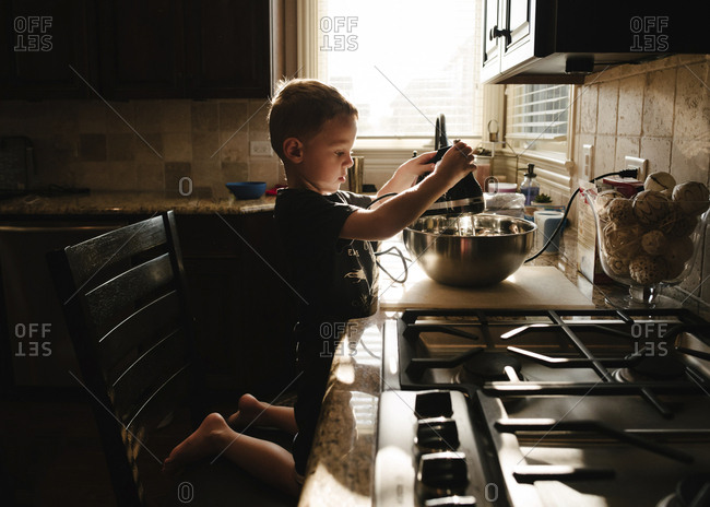 Side view of boy preparing food in kitchen at home