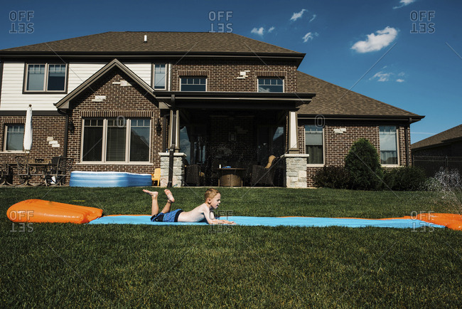 Side view of boy sliding on water slide mat in front yard