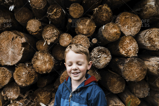 Smiling boy with eyes closed standing by logs