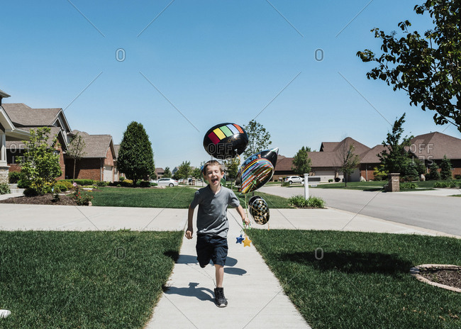 Happy boy with balloons running on footpath against clear blue sky during sunny day