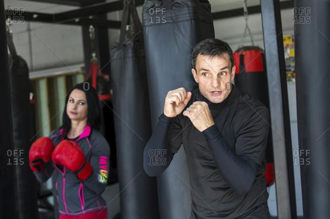 Coach training female boxer in gym