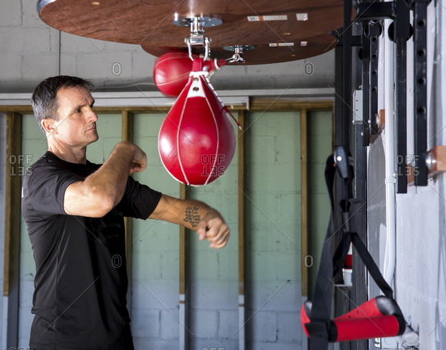 Boxing coach punching speed bag in gym