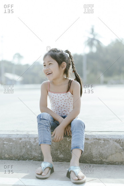 Full length of cheerful girl sitting on retaining wall
