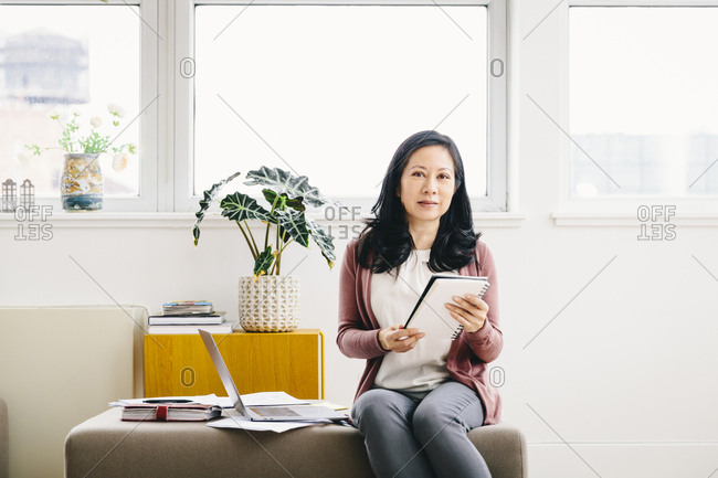 Portrait of confident businesswoman holding spiral notebook while sitting in office